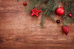 Christmas ornaments and fir tree branch on a rustic wooden background. Xmas card. Happy New Year. Top view. With copy space Stock Photography