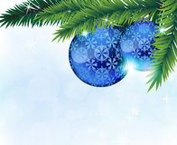 Christmas ornaments and fir tree branches. Fir tree branches with blue baubles on a blue sparkling background Stock Photography