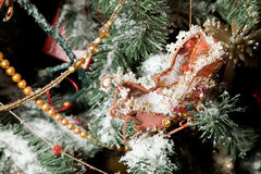 Christmas ornaments in form of sledge on fir-tree Royalty Free Stock Images