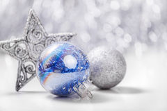 Christmas ornaments on glitter bokeh background. Silver and Blue Christmas ornaments (balls, star) on glitter bokeh background with space for text. Xmas and Stock Image