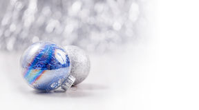 Christmas ornaments on glitter bokeh background. Silver and blue Christmas ornaments on glitter bokeh background with space for text. Xmas and Happy New Year Royalty Free Stock Image