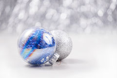 Christmas ornaments on glitter bokeh background. Silver and Blue Christmas ornaments on glitter bokeh background with space for text. Xmas and Happy New Year Royalty Free Stock Images
