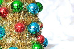 Christmas Ornaments on a gold tinsel tree. With a white background Stock Photos