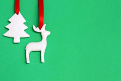 Christmas ornaments on green. Two white Christmas ornaments with red ribbons hanging against a green background.  Christmas tree and reindeer Stock Image