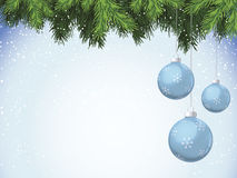 Christmas Ornaments Hanging from Evergreen. Blue Christmas ornaments hanging from evergreen branches. Snow falling dots in background along edges with blue Royalty Free Stock Images