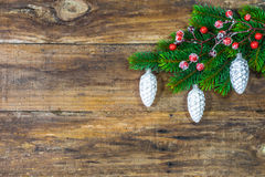 Christmas Ornaments hanging on green fir branch over rustic wooden board. royalty free stock photography