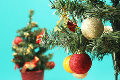 Christmas ornaments hanging from tree. With christmas tree in background Royalty Free Stock Image
