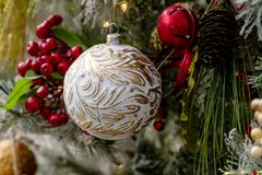 Christmas ornaments hanging on tree. Close up of white and gold antique ornament hanging on decorated Christmas tree Royalty Free Stock Images