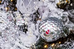 Christmas ornaments hanging on tree. Shiny silver Christmas ornament hanging on frosted white Christmas tree with lights and jewels Stock Photography