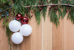 Christmas ornaments on hard wood background with green top frame. Christmas ornaments and jingle bells on hard wood floor background with green leaves top frame Stock Photography