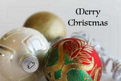 Christmas Ornaments and Merry Christmas text. Red, green, gold, white Christmas ornaments sparkle. Merry Christmas in black, old fashioned letters in upper right Stock Photo