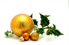 Christmas ornaments - orange ball with green holly. Isolated on white background stock photography