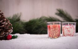 Christmas ornaments with snow, pine tree and candle. Christmas ornaments over a snowy floor, pine tree and red and white candles with a wood background royalty free stock image