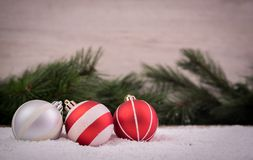 Christmas ornaments with snow and pine tree. Christmas ornaments over a snowy floor with pine tree and wood background Royalty Free Stock Photos