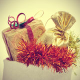 Christmas ornaments. Picture of some christmas ornaments, such a gift a golden sachet and tinsel of different colors in a christmas stocking, with a retro effect Royalty Free Stock Image