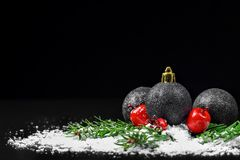 Christmas ornaments with pine tree branches. On a black background Stock Image