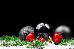 Christmas ornaments with pine tree branches. On a black background Royalty Free Stock Photos