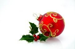 Christmas ornaments - red ball and green holly royalty free stock images