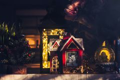 Christmas ornaments on the shelf, little red house, lantern and snow globe. Illuminated with sunlight Stock Photography