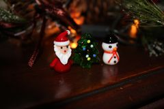 Christmas ornaments sitting on dark wooden piano with fir bows, lights and ribbons Royalty Free Stock Photo