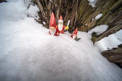 Christmas ornaments in snow. Father Christmas and his helpers outdoors in the snow with tree backdrop setting the mood for Christmas stock photo