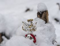 Christmas ornaments in snow. A glass angel holding a star outdoors in the snow with tree backdrop setting the mood for Christmas royalty free stock image