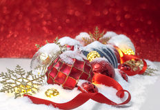 Christmas ornaments  in the snow over red background Stock Images
