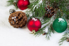 Christmas Ornaments on Snow with Pine Tree Branch Royalty Free Stock Photography