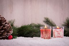 Christmas ornaments with snow, pine tree, red candle and xmas lights. Christmas ornaments with xmas lights and red candle over a snowy floor with pine tree and Stock Photography