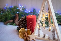 Christmas ornaments with snow, pine tree and xmas lights. Christmas ornaments with xmas lights and dry fruits over a snowy floor with pine tree and wood Royalty Free Stock Photography