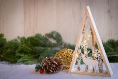 Christmas ornaments with snow, pine tree, and xmas lights. Christmas ornaments with xmas lights over a snowy floor with pine tree and wood background Stock Photo