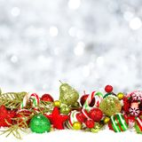 Christmas ornaments in snow with twinkling background Royalty Free Stock Photography