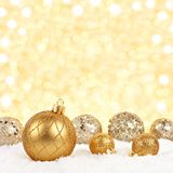 Christmas ornaments in snow with twinkling gold background. Golden Christmas ornaments in snow with twinkling gold background Royalty Free Stock Images