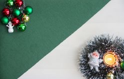 Christmas ornaments, snowman, Santa Claus, New Year`s tinsel, burning candle on a green background. New Year and Christmas background for postcards and Stock Image