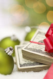 Christmas Ornaments and Stack of Hundred Dollar Bills with Bow Stock Photography