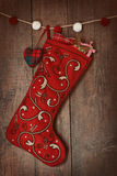 Christmas ornaments in stocking hanging on wood Royalty Free Stock Photos