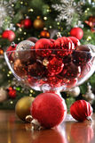 Christmas ornaments on table in front of tree Stock Image
