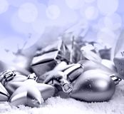 Christmas ornaments on a table in the snow with nice festive bac. Christmas ornaments on a table in the snow with a nice festive background Xmas illuminations royalty free stock photography