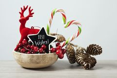 Christmas ornaments and text best wishes. Some different cozy christmas ornaments in a rustic earthenware tray and a black star-shaped signboard with the text stock image