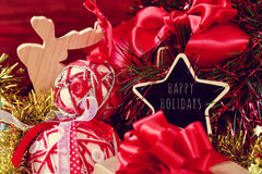 Christmas ornaments and the text happy holidays. Star-shaped chalkboard with the text happy holidays surrounded by a pile of gifts, and some different christmas royalty free stock images