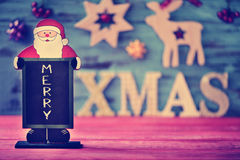 Christmas ornaments and text merry xmas. A chalkboard in the shape of santa claus with the text merry and wooden letters forming the text xmas on a blue rustic Stock Photo
