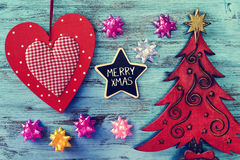 Christmas ornaments and text merry xmas in a star-shaped chalkbo. A star-shaped chalkboard with the text merry xmas written in it on a blue rustic wooden surface Stock Photography