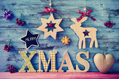 Christmas ornaments and text merry xmas. A star-shaped chalkboard with the text merry and wooden letters forming the text xmas on a blue rustic wooden surface Stock Photography