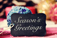 Christmas ornaments and text seasons greetings. Closeup of a black label with the text seasons greetings and on a rustic wooden surface with some different stock photo