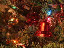 Christmas Ornaments on a Tree. Focusing on a gold ball and a red bell Stock Images