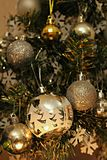 Christmas ornaments on a christmas tree. A close up of golden and silver christmas ornaments on a christmas tree Stock Photos