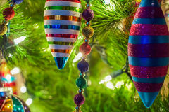 Christmas ornaments on a tree. Christmas ornaments and decorations on a lit Christmas tree stock photos