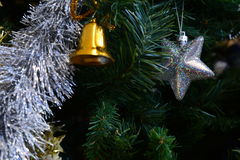 Christmas ornaments. Christmas tree decorations on a tree with globes, tinsel and bells Stock Images