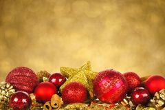 Christmas ornaments with twinkling background. Christmas border of red and gold ornaments with twinkling gold light background Stock Image