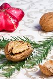Christmas ornaments, walnuts and fir. Cracked walnut on fir branch on holiday napkin with Christmas red star stock photography